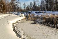 Creek in spring season with open water and snow and ice, wooden bridge and reed in the water, Boden county, Norrbotten, Sweden.