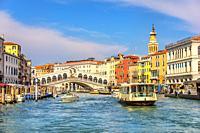 The Rialto Bridge and a vaporetto in a canal of Venice.