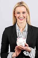 Business woman holding a piggy bank.