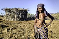 portrait of an old Mucubale woman with traditional brass in front of her hut.