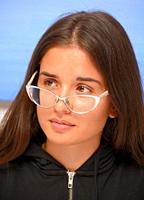 Young dark-haired woman, 30 years old, looking aside over her eye glasses, in Ystad, Sweden.