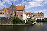 Enkhuizen, small city of northern holland, historic buildings on the bank of the channel, under a blue sky with clouds.