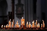 Candles lit by worshippers in a Christian church.