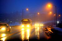 Headlights of cars and a coach bus reflect on wet road on a foggy, blue winter evening in a suburban area. Salo, Finland.