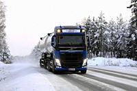 Salo, Finland - December 23, 2018: Volvo FH bulk transport truck up front driving on snowy road in arctic conditions, with high beam lights on briefly...