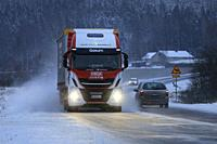 Salo, Finland - December 22, 2018: Biogas fueled Iveco Stralis NP truck L. Retva Oy pulls FREJA trailer along snowy highway in winter evening traffic.
