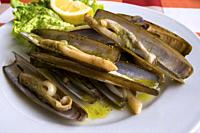 A plate of razor sharp clams (navajas) served in a restaurant at Combarro, Galicia, Spain.