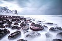 Rocks on the beach modeled by the wind surround the icy sea Unstad Lofoten Islands Norway Europe.