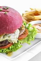 beetroot red bun cheese burger snack set with fries and chilli mayo on white plate.