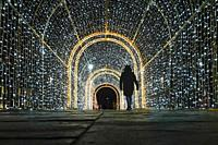 Gdansk, Poland Christmas decorations in a light tunnel at the Forum Mall and pedestrians.