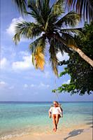 Young caucasian woman sitting in a swing chair, hanging over the beach at a palm tree, Dharavandhoo, Baa Atoll, Maldives, Indian Ocean, South Asia.