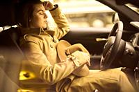 woman sitting in car at driver´s side behind steering wheel with closed eyes, exhausted, relaxed, sleeping, pensive reminiscing emotion, in Munich, Ge...