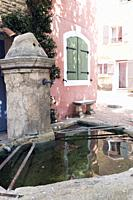 Traditional stone fountain and basin with clear rippling water, reflecting shutters in pastel shades on the pretty pink and cream sunlit buildings opp...