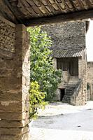 Traditional Roman terracotta roof tiles from above and below with steps and rustic stonework in a sun filled courtyard in Cabrières-d'Avignon, Vauclus...