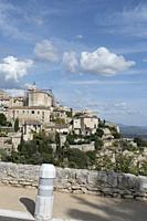 Sky blue day with puffy white clouds and long shadows, tumbling down the hillside past the historic mountain town of Gordes in the Vaucluse, Provence-...