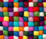 Colorful felted little balls full frame decorative background.