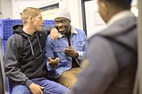 young men talking in public transport, in Munich, Germany.