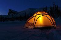 Camping in winter season at night, lantern shining in the tent, Mount Skerfe and Sarek national park in background, Jokkmokk county, Sarek national pa...