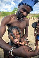 Himba demonstrating how they remove child's bottom teeth - Damaraland, Namibia, Africa.