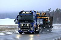 Salo, Finland - January 4, 2019: Blue Volvo FH truck of M. Toivonen Oy hauls tracked excavator on trailer along wet highway on a foggy day of winter.