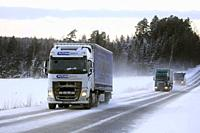 Salo, Finland - January 18, 2019: White Volvo FH of Rutomcargo, Germany, green Scania truck and a bus travel through Finnish winter scenery at dusk.