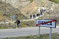 Road sign at the exit of the city of Cuenca, cyclist and hikers in background, Castile-La Mancha, Spain