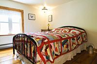 Double bed with bright multicoloured patterned bedspread and wrought iron headboard and footboard in upstairs guest bedroom, inside an old 1892 Canadi...