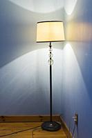 Lit antique pedestal lamp in blue bedroom on upstairs floor inside an old 1807 Canadiana style fieldstone home