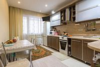 Interior spacious kitchen in a residential apartment.