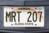 "Hawaii car license plate. Hawaiian license plate on back of car with rainbow and text """"Aloha state""""."