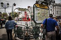 Paris Metro entrance with de Moulin Rouge in the back.