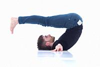 Casual dressed young adult man stretching on white background.
