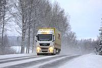 Salo, Finland - January 27, 2019: MAN semi trailer of Transport Forsstrom pulls DHL trailer on highway in snowfall, bright auxiliary lights on briefly...