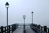 Views of the lonely wooden pier in the fog with two lampposts and old clock on the lake Konigsee in Germany.