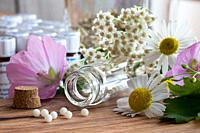 A bottle of homeopathic pills with chamomile, yarrow and other flowers on a wooden table.