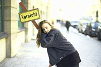 woman leaning on post at street in city, letters Vorsicht, in Munich, Germany