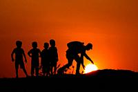 Silhouette of man with the kids touching Sun, Maharashtra, India.