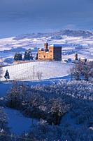 Grinzane Cavour, Piedmont, Italy View of the Castle, Unesco symbol, illuminated by an evocative beam of light, surrounded by marvelous hills and snowy...