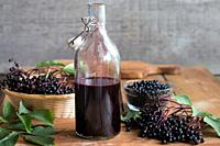 A bottle of homemade elderberry syrup on a wooden table, with fresh elderberries in the background.