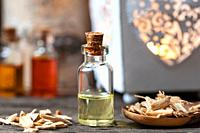 A bottle of essential oil with cedar wood chips.