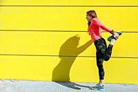young woman stretching on a yellow wall before running.