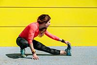 young woman stretching on the floor in front of a yellow wall before running.