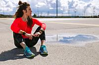 Young woman resting sitting on the floor after run listening music with headphones.