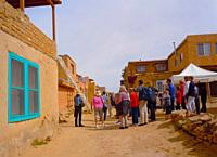old Amerind village atop mesa, continuously inhabited by Acoma people for 2000 years. Visitors being shown the kiva ladder (into ceremonial chamber). ...