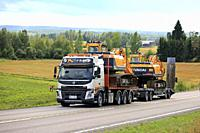 Jamsa, Finland - August 23, 2018: Volvo FMX truck hauls two Huyndai Robex 180 LC-9 and 160 LC-9 crawler excavators on trailer along road as wide load.