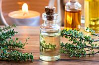 A transparent bottle of thyme essential oil with fresh thyme twigs and a candle in the background.