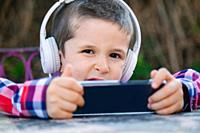 boy listening to music with withe headphones on the outside.