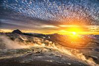 Woman standing by geothermal hot springs, mud pots and fumaroles, Namaskard close to Lake Myvatn, Northern, Iceland.