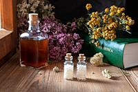 Two bottles of homeopathic globules with dried herbs and a materia medica, i. e. a list of remedies and their therapeutic properties.