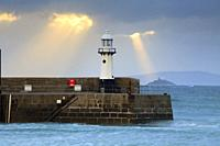 Shafts of light behind the lighthouse on Smeaton's Pier at St Ives in Cornwall, with Godrevy Island and lighthouse in the distance. The image was capt...